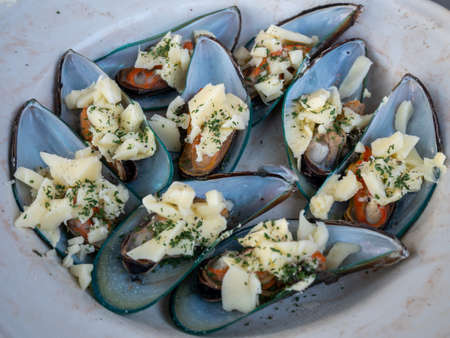 Mussels with cheese and herbs on the plate