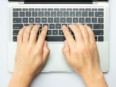 Modern white office desk table with Man hands working on the laptop. Stock fotó