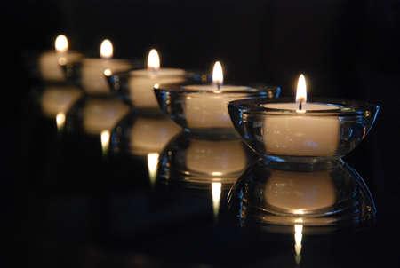 kerzen: Gruppe von brennenden Kerzen auf schwarzem Hintergrund