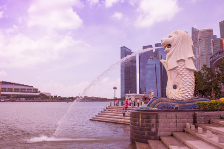 SINGAPORE - APRIL 14,2018 : The Merlion fountain, symbol of Singapore which many people take photo and this place in front of the business building and view of Marina Bay in Singapore.