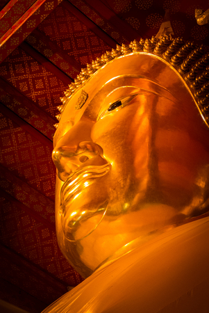 Look up view and close-up face of golden buddha statue in buddhist hall, Thailand.