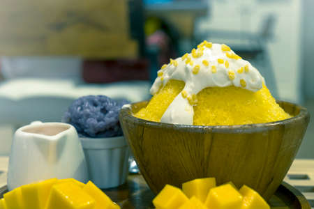 Close-up bingsu or shaved ice dessert topped with coconut fresh cream and mango sliced served with sticky rice and mango sauce, sweet dessert in Korean style.