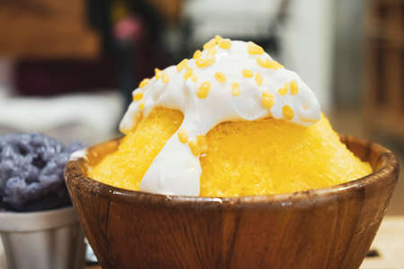 Close-up bingsu or shaved ice dessert topped with coconut fresh cream and served with sticky rice, sweet dessert in Korean style. 免版税图像