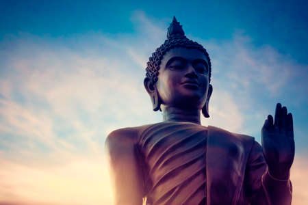 Vintage tone portrait black buddha statue and sky on background in Thailand.