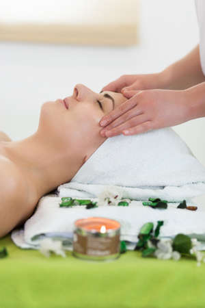 Young smiling beautiful woman is getting facial massage in spa, side view, pretty hands, portrait frame orientation