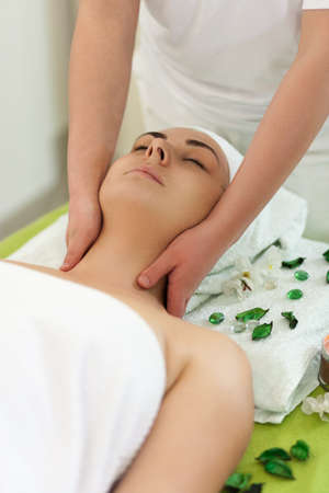 Young smiling beautiful woman is getting facial massage in spa, pretty hands, portrait frame orientation