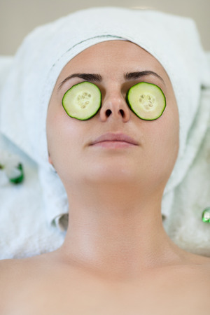 Young woman enyoing facial treatment in spa with sliced cucumbers on her eyes and towel on head. Bright scene, look from top