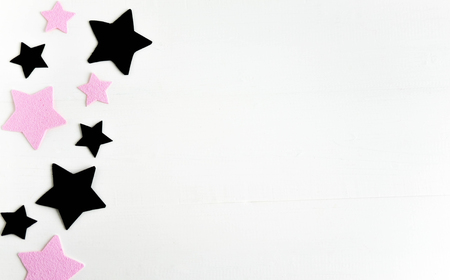 Stars of black and pink color on a white wooden background. Background for teens with stars. 版權商用圖片
