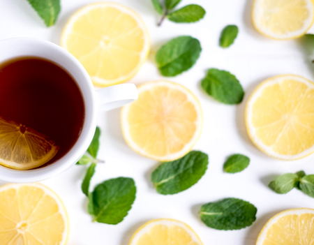A cup of tea along with mint and lemon. Cold tea. Natural cures for the disease. Black tea with lemon on a white background Stockfoto