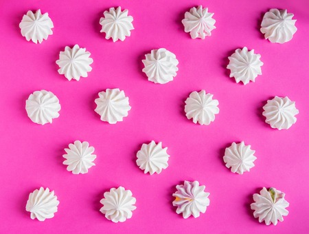 Pattern with meringues on a pink background. Basis for design with multicolored meringues on a pink background.