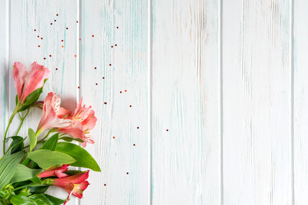 Background for text banner on a dark wooden background with pink flowers. Blank, frame for text. Greeting card design with flowers. Aalstroemeria on wooden background.