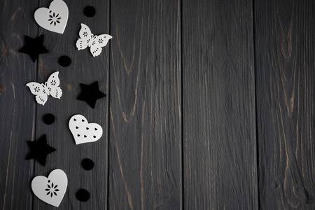 Stars of black color and white hearts and butterflies on a gray wooden background. Background for teens with stars. 版權商用圖片
