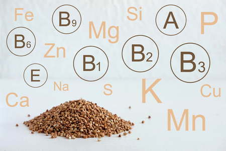 Buckwheat with vitamins and minerals that it contains. Hill of buckwheat on a light background. Healthy and healthy food.