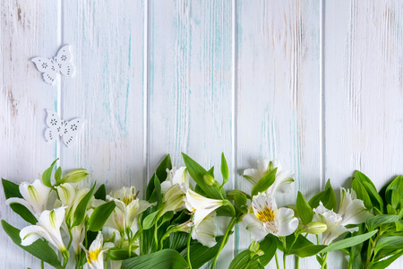 Background for text banner on a light wooden background with white flowers and butterflies. Blank, frame for text. Greeting card design with flowers. Stock Photo