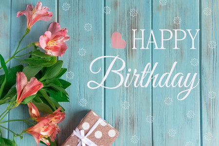 Greeting card with the inscription happy birthday. Congratulatory greeting to the girl, mother with flowers and a gift on a wooden background Stock Photo
