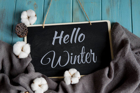 Hello winter postcard. Winter banner with warm gray shawl, cotton flowers on a blue background