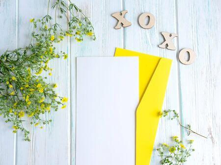 嘲笑白纸和信封在黑暗的木背景与白色颜色自然花。空白,文本的框架。与花的贺卡设计。