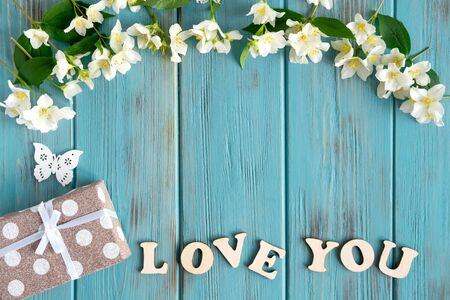 Jasmine flowers, gift and the inscription Love you on a wooden background. Spring congratulatory banner. Greeting card design with jasmine flowers.