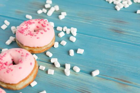 Photo of two donuts covered with pink icing on a blue wooden background with a place for an inscription. Delicious donuts