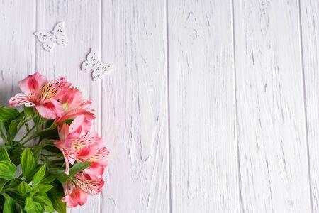 ピンクの花と蝶と明るい木製の背景にテキストバナーの背景。空白、テキストの枠。花とグリーティングカードのデザイン。木製の背景にアルストロメリア。 写真素材