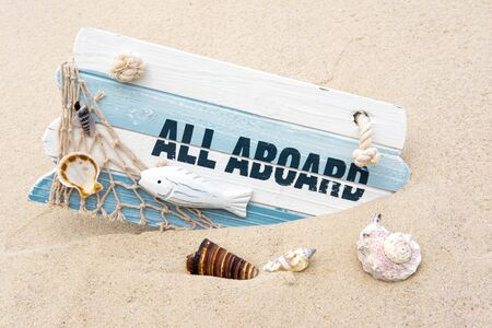 Photoconcept sea travel. Blackboard with the words all aboard, seashells in the sand. Marine photo.