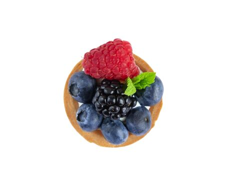 Tartlet with berries of raspberry, bilberry, blackberry, blueberry isolated on white background. Cake with berries, mint leaf and cheese cream. Standard-Bild