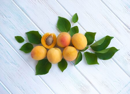 Congratulatory banner with apricots on a wooden background with a place for copy space. Apricots with leaves close up.