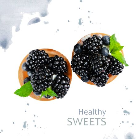 Tartlet with blackberries on a white background with watercolor pattern. Conceptual photo of useful sweets with berries.