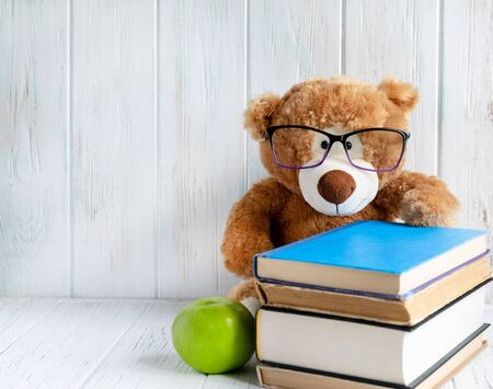 Photo of a stack of books with a bear, an apple and a place for an inscription on a wooden background. Back to school concept. Kids banner for text with books and bear.