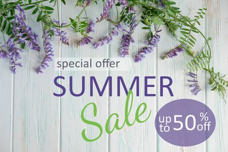 Banner summer sale. Summer wildflowers with the inscription summer sale on a wooden background. Stock Photo