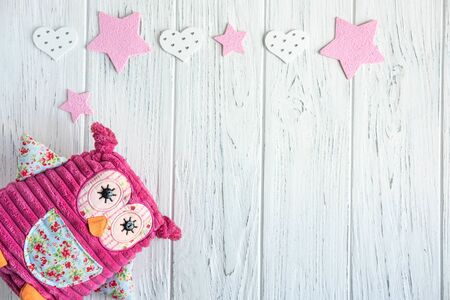 Design greeting card for girls. Toy owl and butterflies on a wooden background.