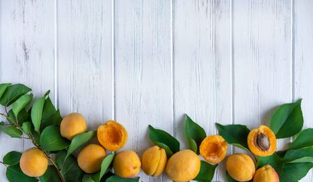 Background with apricots. Photo of fresh apricot with green leaves and place for copy space on a white wooden background. Apricots close-up. Agriculture, advertising, diet and healthy nutrition