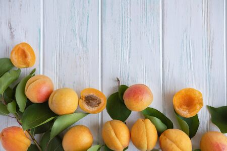 Ripe apricot fruit with green leaves close-up on a light wooden background. Summer fruit containing pectin.