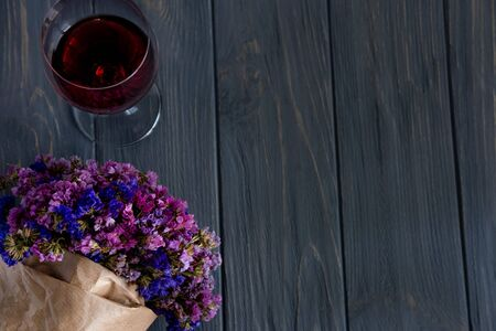 A glass of red wine close-up along with a bouquet of wildflowers on a gray wooden background. Фото со стока