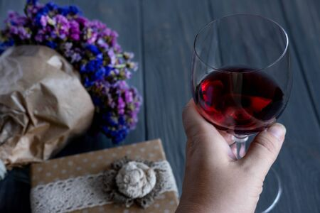 A glass of red wine close-up along with a bouquet of wildflowers and gift boxes on a dark wooden background. Фото со стока