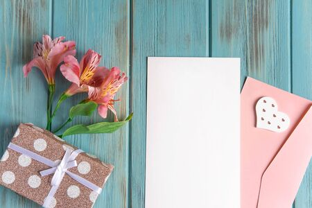Mock up blank paper and envelope on blue wooden background with natural flowers of pink color. Blank, frame for text. Greeting card design with flowers. Alstroemeria background.