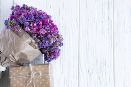 Bouquet of dried wildflowers with gift box on a wooden background. Greeting card