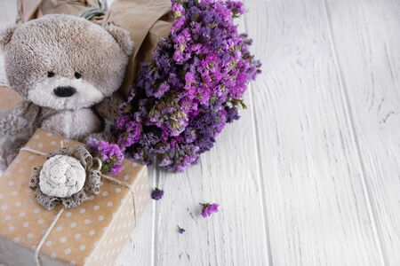 Bouquet of dried wildflowers with gift box and bear on a wooden background. Greeting card