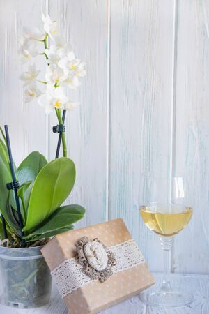 Glass of wine with white orchid flower, gift box. Greeting card for birthday