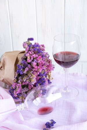 A bouquet of dried wildflowers on a pink fabric background with a glass of wine. Floral greeting background for greeting card Фото со стока