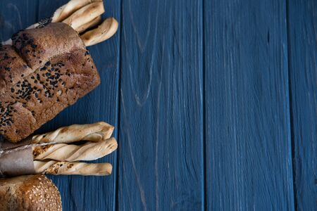 Background for a bakery, a department for the sale of bakery products. Photo of bread and bread sticks on a gray wooden background