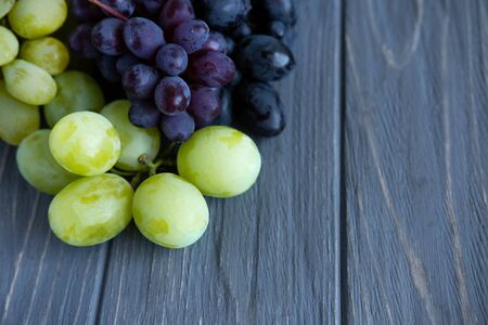 Bunches of grapes of different varieties on a gray wooden background. Green, blue and pink grapes close-up