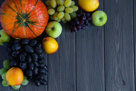 Autumn harvest of vegetables and fruits on a dark wooden background with a place for inscription. Pumpkin, peach, apples, grapes.