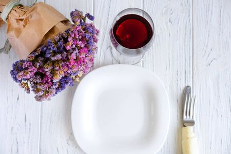 Table setting. Plate on wooden background with gift box and flowers.