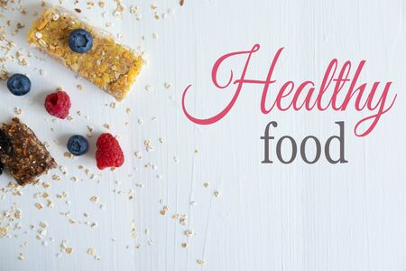 Healthy food. Granola cereal bars close-up with fresh raspberries and blackberries. A balanced diet for weight loss. Фото со стока