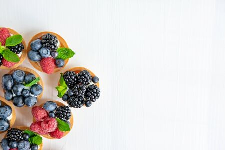 Background with tartlets with raspberries, blueberries, blackberries. Frame for text with beautiful pastries.