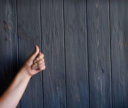 Creative conceptual photo of a hand that shows ok against a background of gray wooden background.