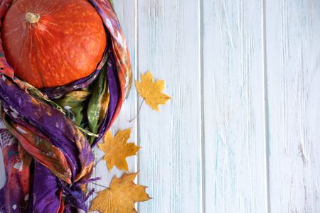 Autumn background. Bright pumpkin in a scarf with maple yellow leaves on a white wooden background.