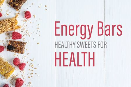 Energy bars healthy sweets for health. The inscription on a white wooden background with granola and fresh raspberries. Фото со стока