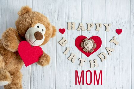 Happy birthday mom. Greeting card design for moms birthday with a teddy bear and a heart. Happy mothers day